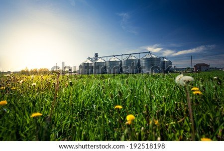 Beautiful photo of grain elevators in meadow at sunset - stock photo