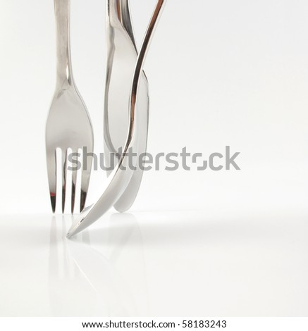 Beautiful photo of stainless steel knife fork and spoon on white - stock photo