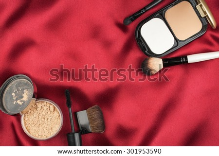 Beautiful picture of cosmetic  on red silk, with space for your text - stock photo