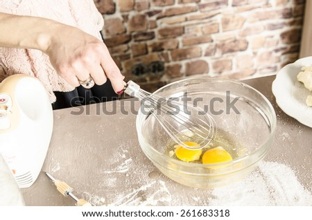 Beautiful picture of eggs in a white bowl with beaters near yolk - stock photo