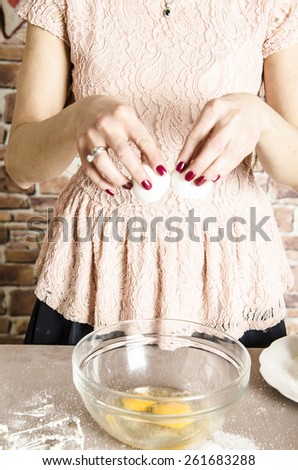 Beautiful picture of woman that beating eggs to a bowl. Taking eggs in hands - stock photo