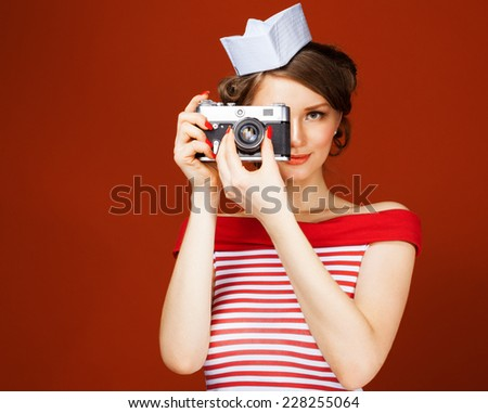 Beautiful pin-up girl holding a vintage camera and directs it straight to the camera. Red background, close up - stock photo