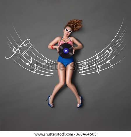 Beautiful pin-up girl in retro bikini and sunglasses, holding an LP microgroove vinyl record and sitting on musical staff chalk drawings background, top view.