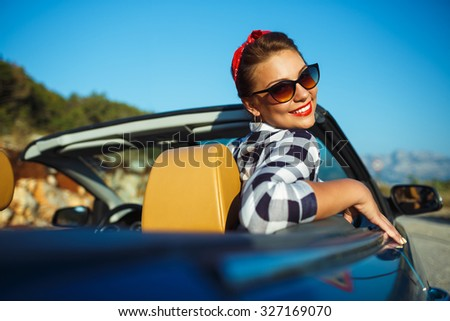 Beautiful pin up woman sitting in cabriolet, enjoying trip on luxury modern car with open roof, fashionable lifestyle concept