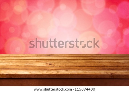 Beautiful pink bokeh background with wooden table - stock photo