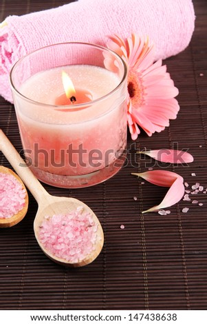 Beautiful pink candle with flower and towel on bamboo mat