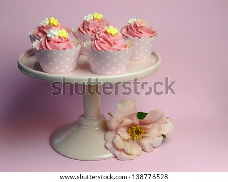 Beautiful pink decorated cupcakes on pink cake stand for birthday, wedding or female special event occasion. - stock photo