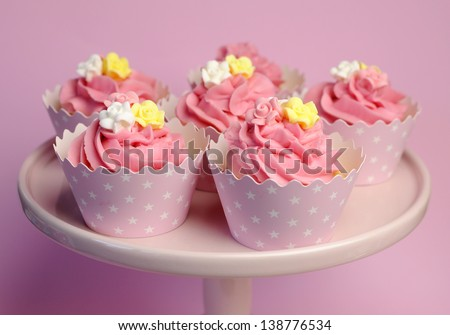 Beautiful pink decorated cupcakes on pink cake stand for birthday, wedding or female special event occasion, with pink, yellow and white fondant roses and pink star cups. - stock photo