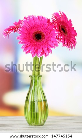 Beautiful pink gerbera flowers in vase on wooden table - stock photo
