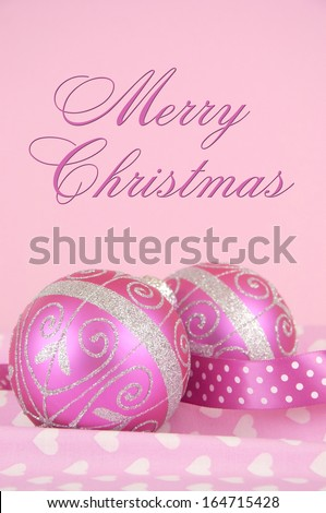 Beautiful pink Merry Christmas bauble decoration ornaments close up against a pink heart and polka dot ribbon background. Selective focus, with Merry Christmas script text. - stock photo