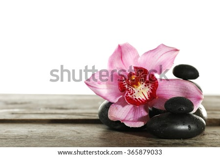 Beautiful pink orchid and spa stones  isolated on white