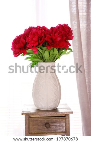 Beautiful pink peonies in vase on wooden table