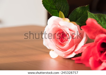 Beautiful pink rose on wooden table