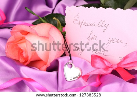 Beautiful pink rose with heart pendant - stock photo