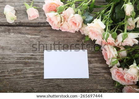 Beautiful pink roses and a greeting card on a wooden table - stock photo
