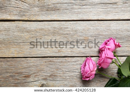 Beautiful pink roses on a grey wooden table - stock photo