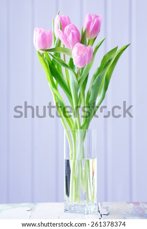 Beautiful pink tulips in vase on table on wooden background