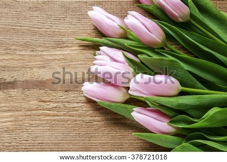 Beautiful pink tulips on wooden background. Copy space - stock photo
