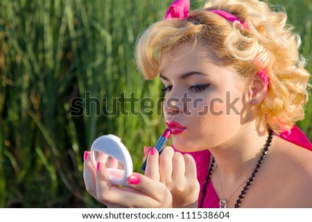 Beautiful pinup girl holding a mirror and checking makeup