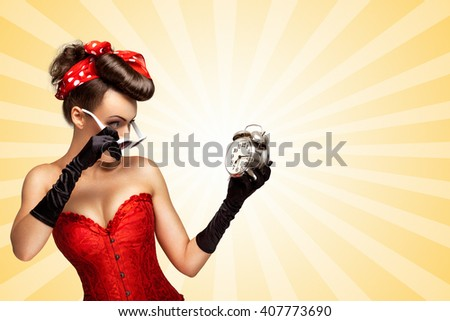 Beautiful pinup girl in a red vintage corset being late in the morning and holding a retro alarm clock in her hand on colorful abstract cartoon style background. - stock photo
