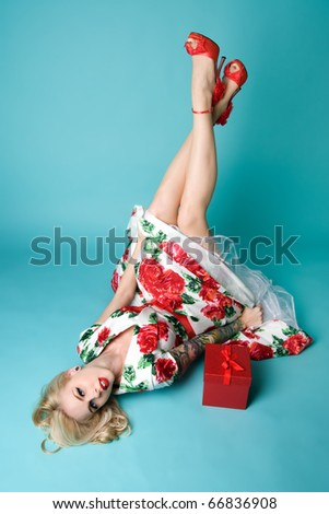 Beautiful pinup model with Christmas gift - stock photo