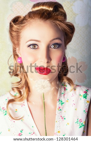 Beautiful Pinup Woman With Retro Hair Style And Makeup Blowing Seeds On A Dandelion Flower While Standing Against A Floral Wallpaper Design In A Spring Beauty Concept - stock photo