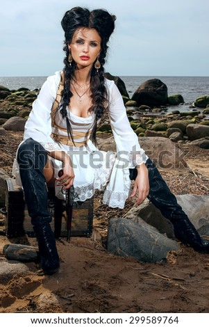 Beautiful pirate woman sitting on the beach with a classic pistol in her hand - stock photo