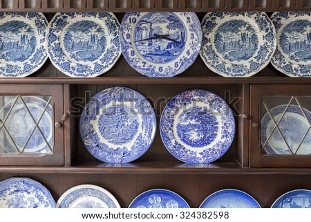 Beautiful plate collection on wooden cabinet . - stock photo