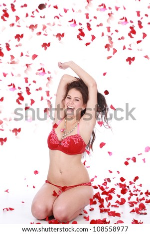 Beautiful playful brunette woman playing with red falling rose petals sitting on white isolated background wearing sexy red lingerie underwear