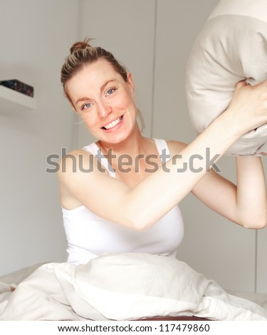 Beautiful playful woman sitting in her bed poised to throw a pillow during a mock fight with a look of glee on her face