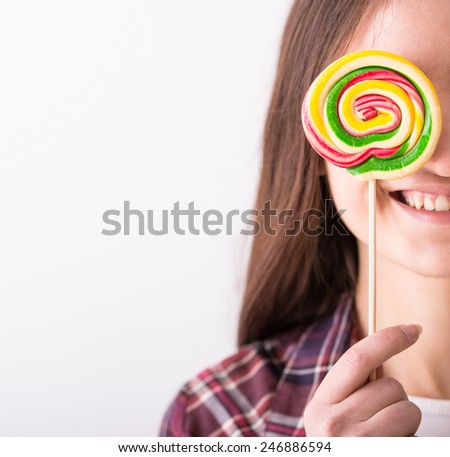 Beautiful playful young woman with colorful lollipop on grey background.