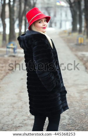 Beautiful plus size blonde woman wearing red hat and fur coat closeup outdoor portrait