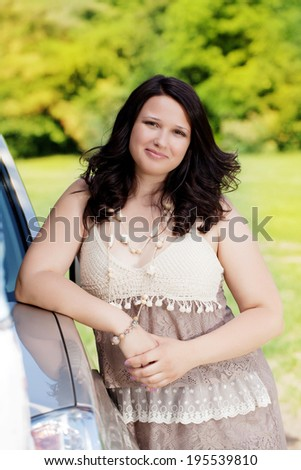Beautiful plus size model outdoors near car  - stock photo
