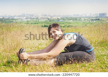 Beautiful plus size woman stretching outdoor  - stock photo