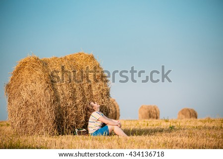 Beautiful Plus Size Young Woman In Shirt Sit Near Hay Bales In Summer Field Meadow At Blue Sly Background - stock photo