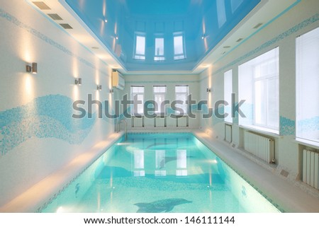 Beautiful pool with images of dolphins at bottom and clear water in big room. - stock photo