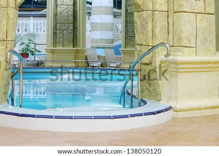 Beautiful pool with pure blue water with and big stone columns. - stock photo