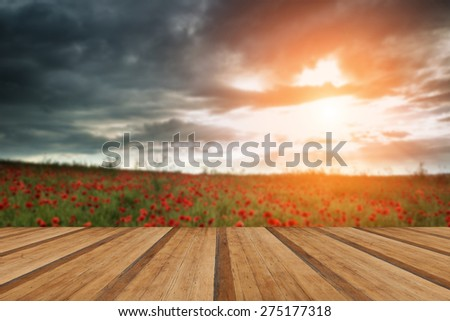 Beautiful poppy field landscape during Summer sunset with dramatic sky with wooden planks floor - stock photo