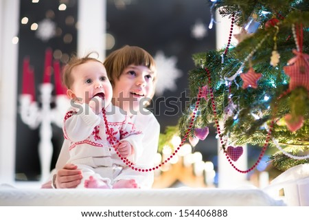 Beautiful portrait of a brother and baby sister in a dark living room next to a Christmas tree with candles and lights - stock photo