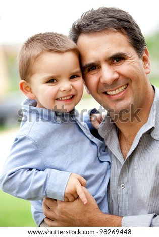 Beautiful portrait of a father and son smiling - outdoors - stock photo