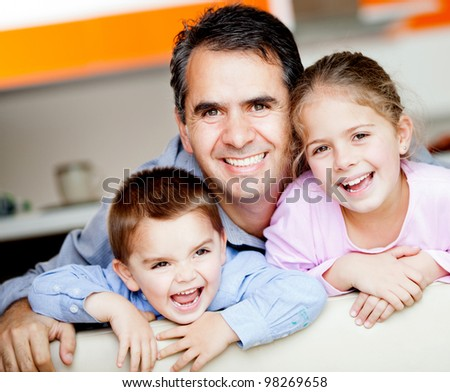 Beautiful portrait of a father with his to kids at home - stock photo