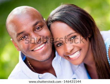 Beautiful portrait of a happy couple smiling outdoors  - stock photo