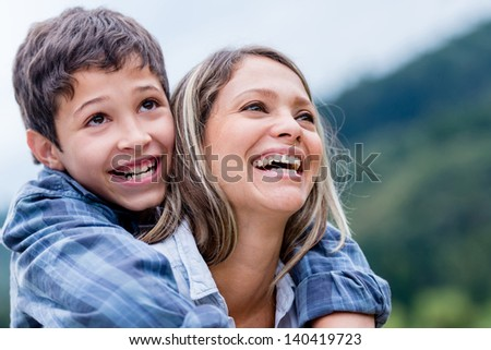 Beautiful portrait of a happy mother and son looking away outdoors