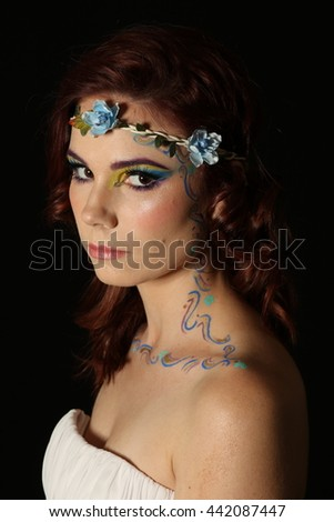 Beautiful portrait of a lovely redhead model with long curly hair and fairy type avant-garde makeup, wearing a white strapless dress on a black background