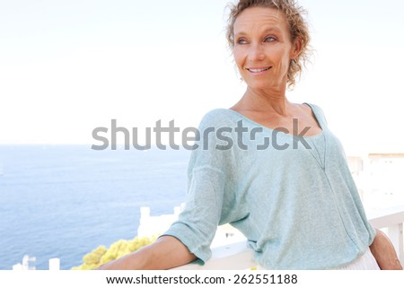 Beautiful portrait of a mature attractive woman relaxing in her holiday resort hotel balcony, contemplating the sea and blue sky on a summer vacation, outdoors. Beauty and lifestyle and well being.