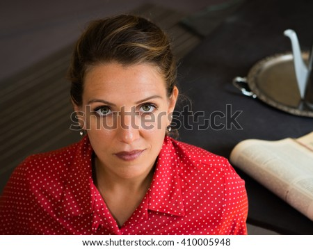 Beautiful portrait of a serious woman in a red dress at tea time looking to the camera - retro style - stock photo