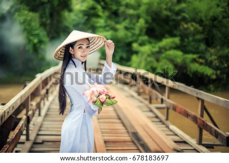 Beautiful Portrait of Asian girls with Ao-Dai Vietnam traditional dress costume woman ,Walk the bridge with Lotus,  at VIetnam.