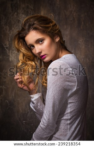 Beautiful portrait of blonde girl on a brown background - stock photo