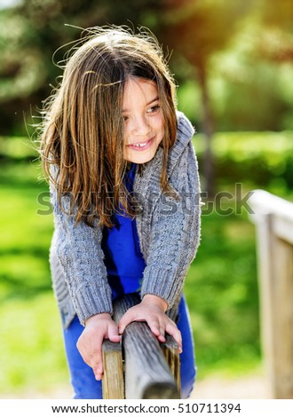 beautiful portrait of cute child playing with greenery in the background