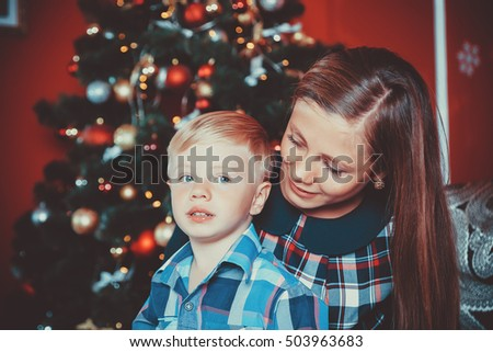 beautiful portrait of happy mother and son on the background of the Christmas tree in new year room. The idea for postcards. Soft focus. Shallow dof